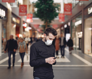 Masked man texting in the marketplace