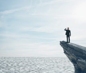 Man stands on cliff and looks out over open ocean